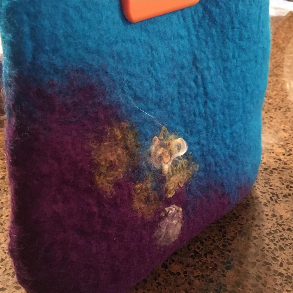 detail of deep purple and teal wool felted handbag, showing gold and green wool embellishments.